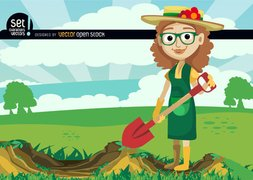 Girl digging with shovel in green field